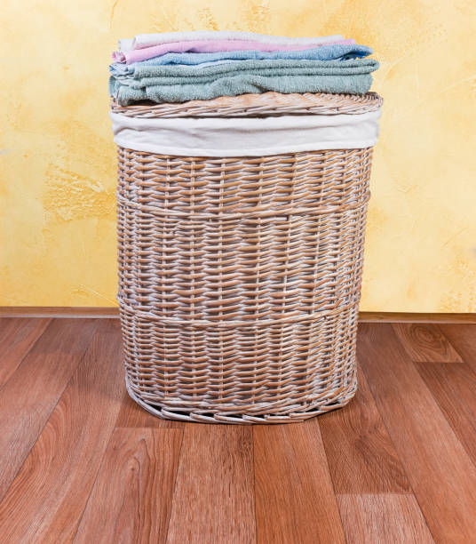 Wooden wicker laundry basket on floor and bath towels stock photo