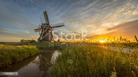 Dutch wooden windmill grass and flowers at sunset in summer field with flowers and beautiful sky