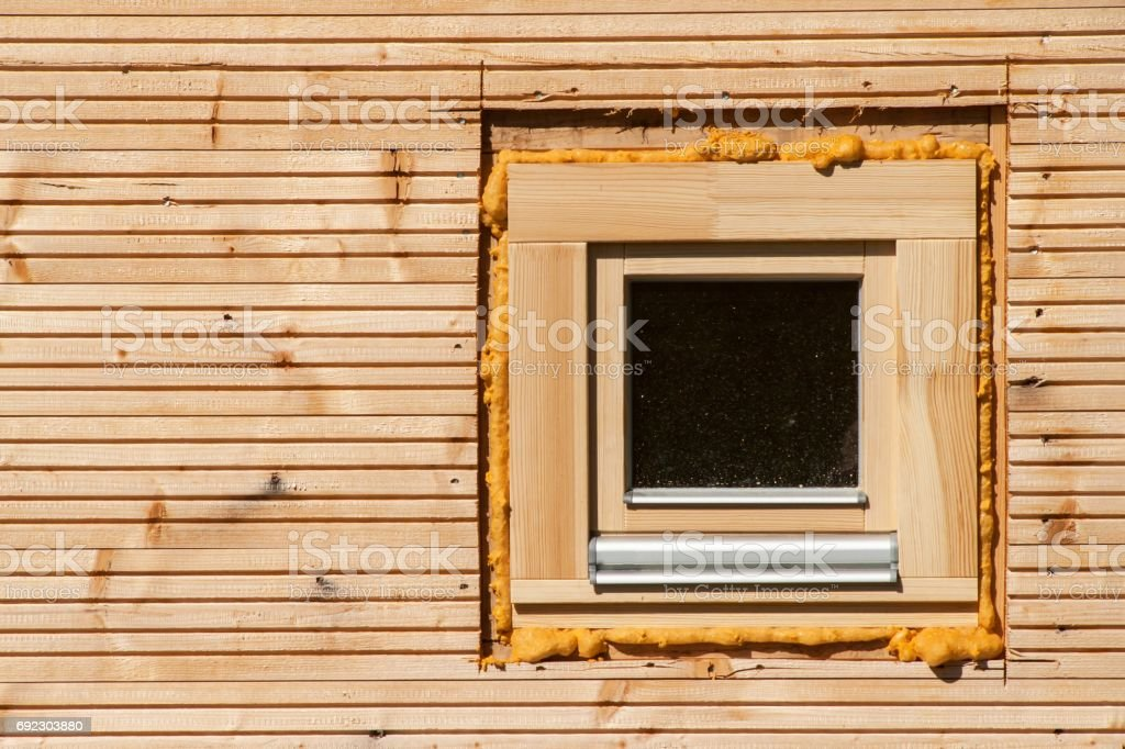Wooden window. Foam window insulation on wooden construction. stock photo