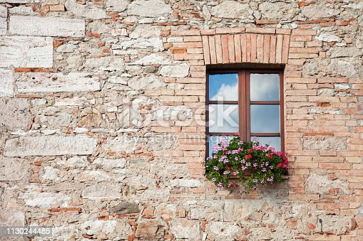 Wooden window on stone wall of ancient italian country house and authentic villa. Window has blue sky reflection and pink, red flowers on decorated windowsill. Background with free space for text.
