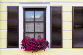 Wooden window with shutters and flowers. Architecture