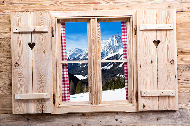 Wooden window with snowy mountain reflections Wooden window with snowy mountains as reflections apres ski stock pictures, royalty-free photos & images