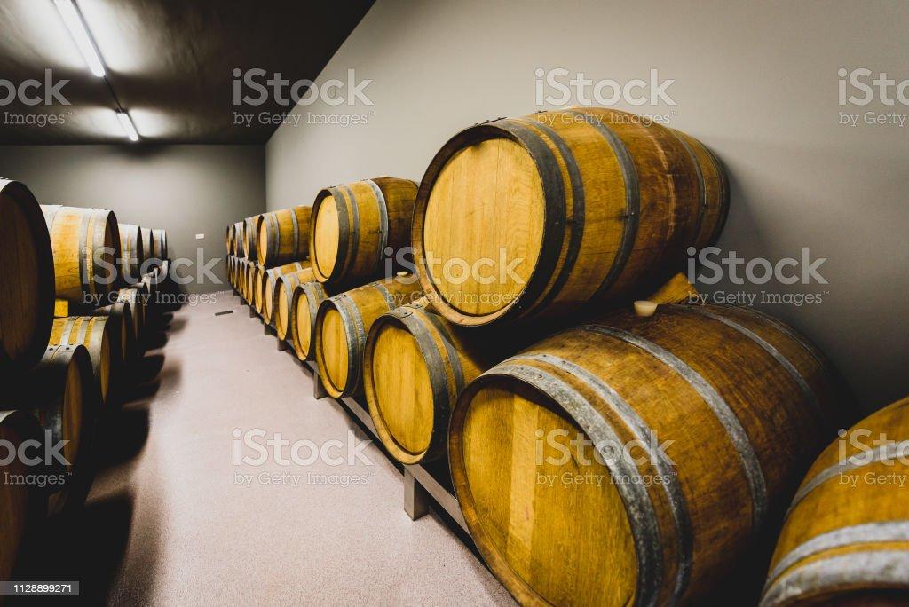 Wooden wine barrels stacked in modern winery cellar in Spain. Modern,...