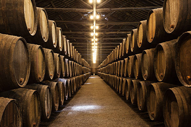 Wooden wine barrels stacked in neat lines in a port Barrels in the wine cellar, Porto, Portugal cellar stock pictures, royalty-free photos & images
