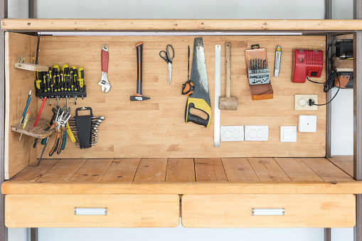 Wooden workbench at workshop. Lot of different tools for diy and repair works. Wood desk for product display. Copyspace. Labour day.