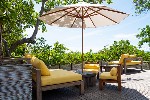 Wooden, yellow sofa couch with umbrella at the outdoor patio. With green tree and blue sky nature background.
