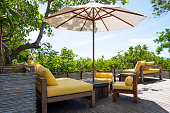 istock Wooden, yellow sofa couch with umbrella at the outdoor patio. With green tree and blue sky nature background. 1265245145
