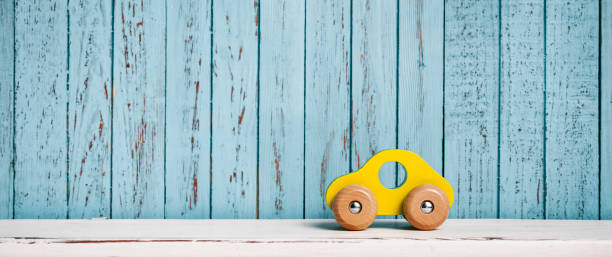 Wooden, yellow toy car on white shelf and blue planks stock photo