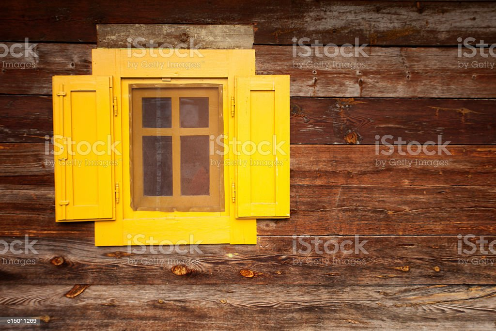 Wooden yellow window at brown wooden wall stock photo
