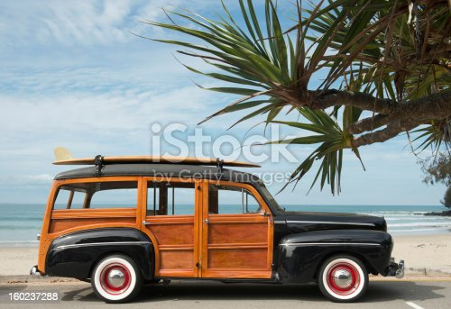 vintage woodie car with surfboard on the roof parked
