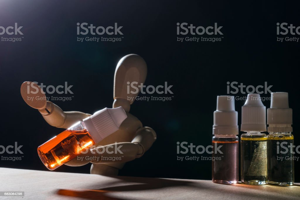 wooding figure selling e-liquid and electronic cigarette. foto de stock royalty-free