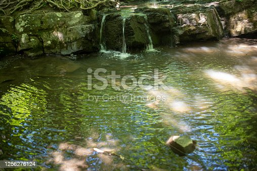 Beautiful surreal full frame nature image of forest waterfall, rock formations and rippling stream reflecting trees and blue sky with dappled sunlight and copy space