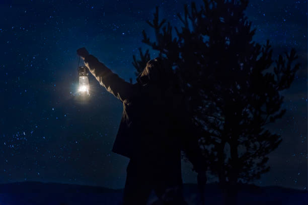 Woodman Man holding gas lamp in forest under stars at night in forest Woodman Man holding gas lamp in forest under stars at night in forest lantern stock pictures, royalty-free photos & images