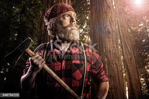 A portrait of a woodsman with an axe in the forest