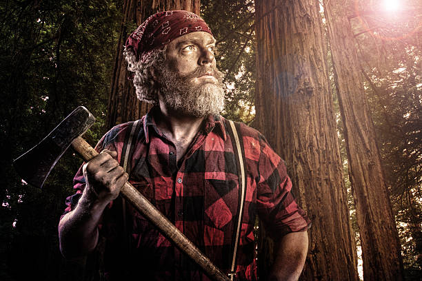 woodsman with axe in the forest - macho fotografías e imágenes de stock