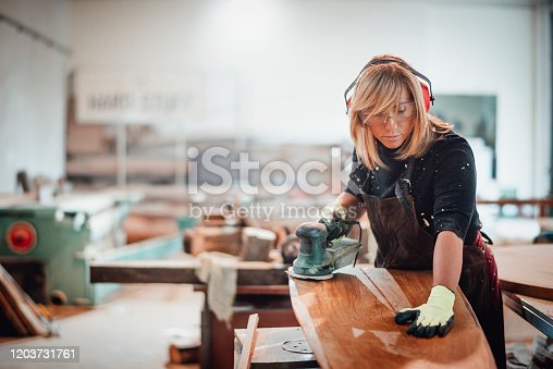 Girl carpenter using an orbit sander to sand down a wooden panel on a work bench in a workshop.
