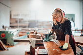 istock Woodworker using a hand sander to sand down a wooden surface 1203731761