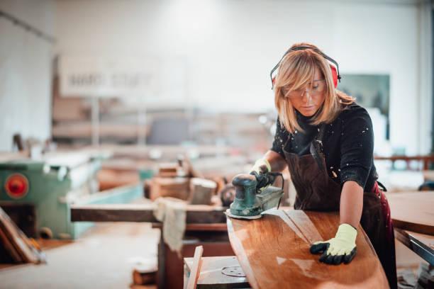 Holzarbeiter mit einem Handschleifer, um eine Holzoberfläche zu schleifen – Foto