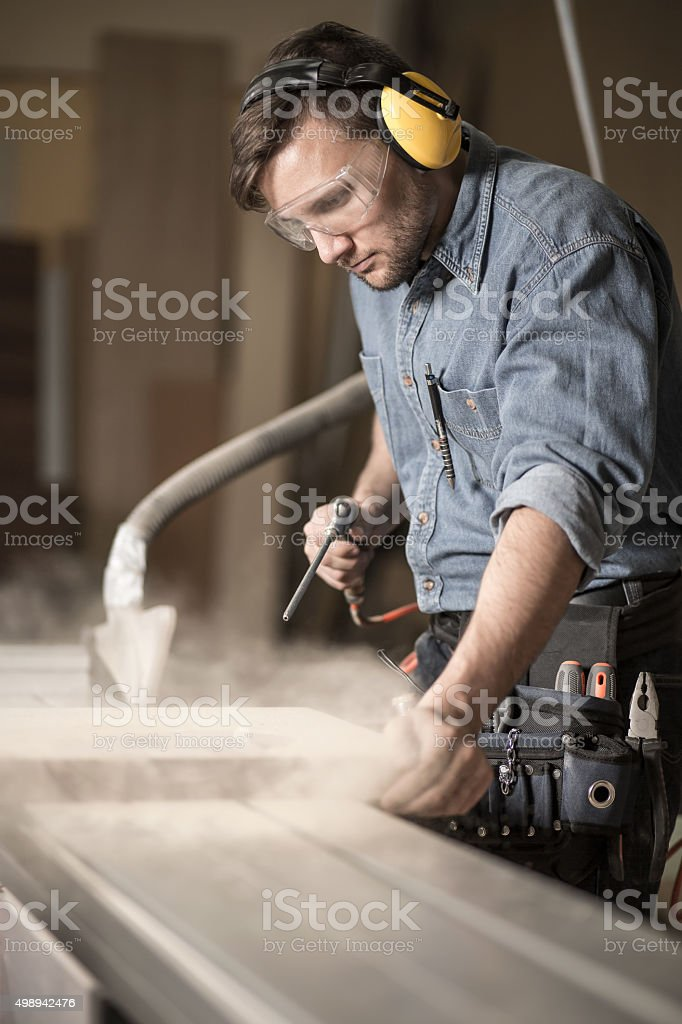 Woodworker wearing muffs and glasses stock photo