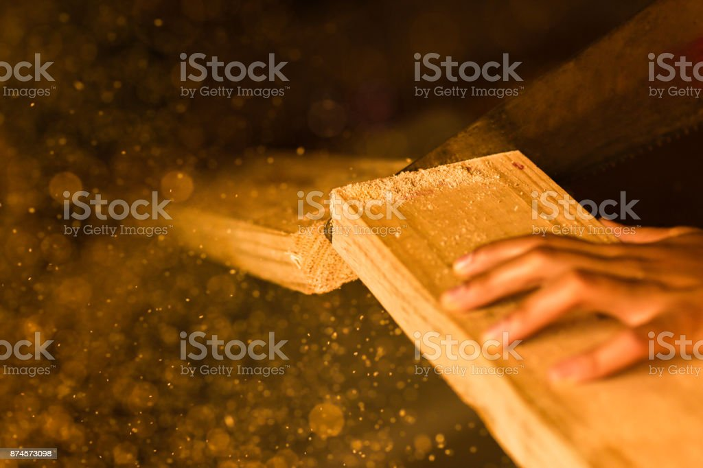 Woodworking with a handsaw and sawdust in the air stock photo