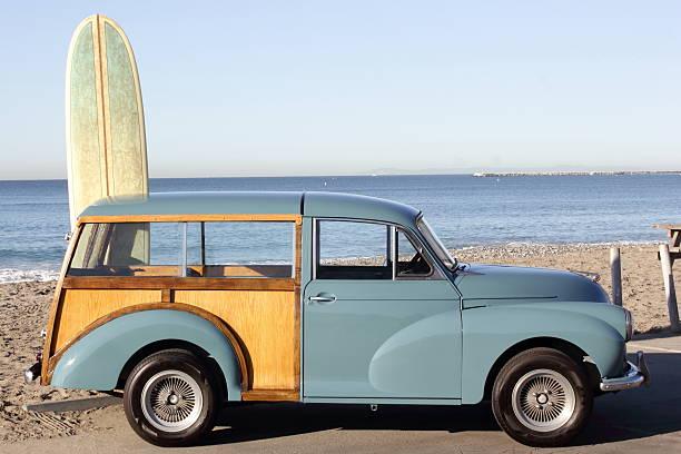 woody with surfboard in background - kombi stock-fotos und bilder