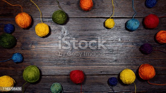 A background with colorful wool balls on the wooden table