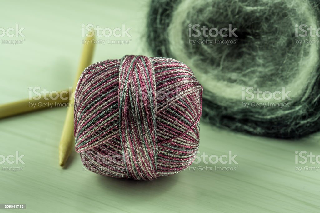 Wool for knitting with needles on a wooden table stock photo