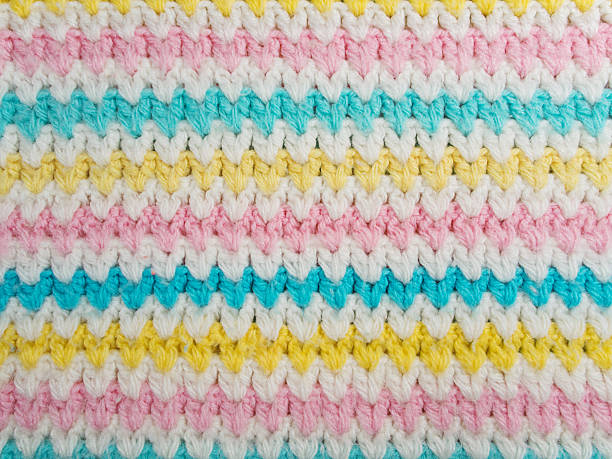 Wool with Pastel Colors Hand-knitted pastel colored wool background in close up. There are white, yellow, pink and baby blue colored stripes at the pattern. baby blanket stock pictures, royalty-free photos & images