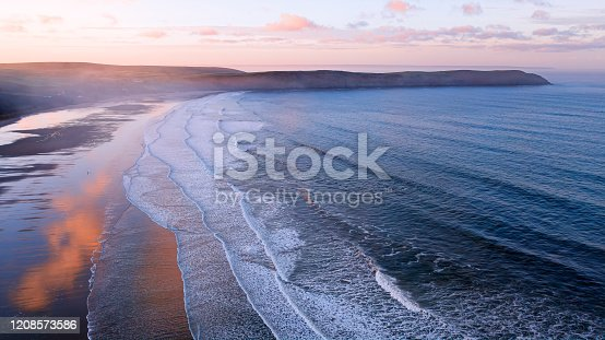 Aerial view of Woolacombe beach Devon England at dawn, waves breaking on a beach where the sunlit clouds are reflected in the standing water. Baggy point is in the background, hazy through the spray from the waves.