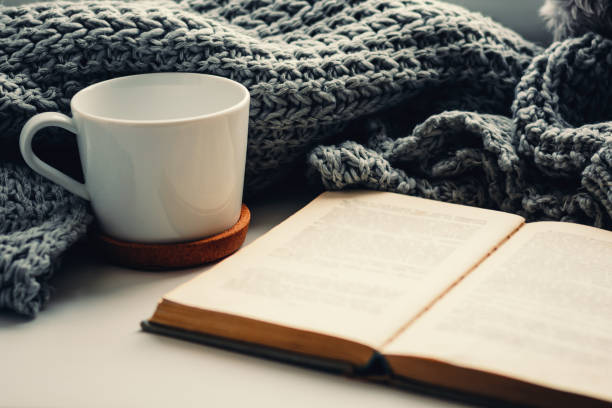 woolen scarf, a cup of tea and book on the windowsill. hygge and cozy autumn concept - hygge imagens e fotografias de stock