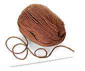 Woolen skein of brown yarn and crochet hook isolated on white background