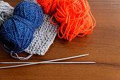 Woolen thread, knitting, knitting needles on wooden table