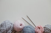 Balls of woolen yarn and knitting needles on grey background. Flat lay style. Place for text.