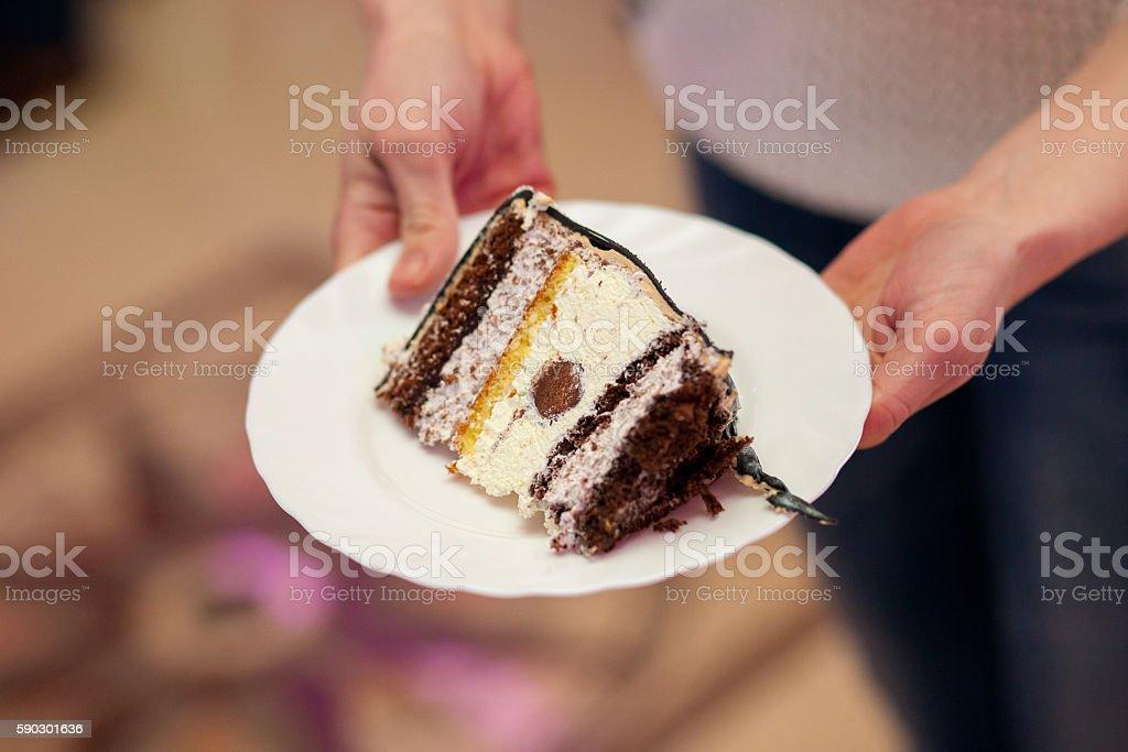 Wooman holding piece of cake on plate royaltyfri bildbanksbilder