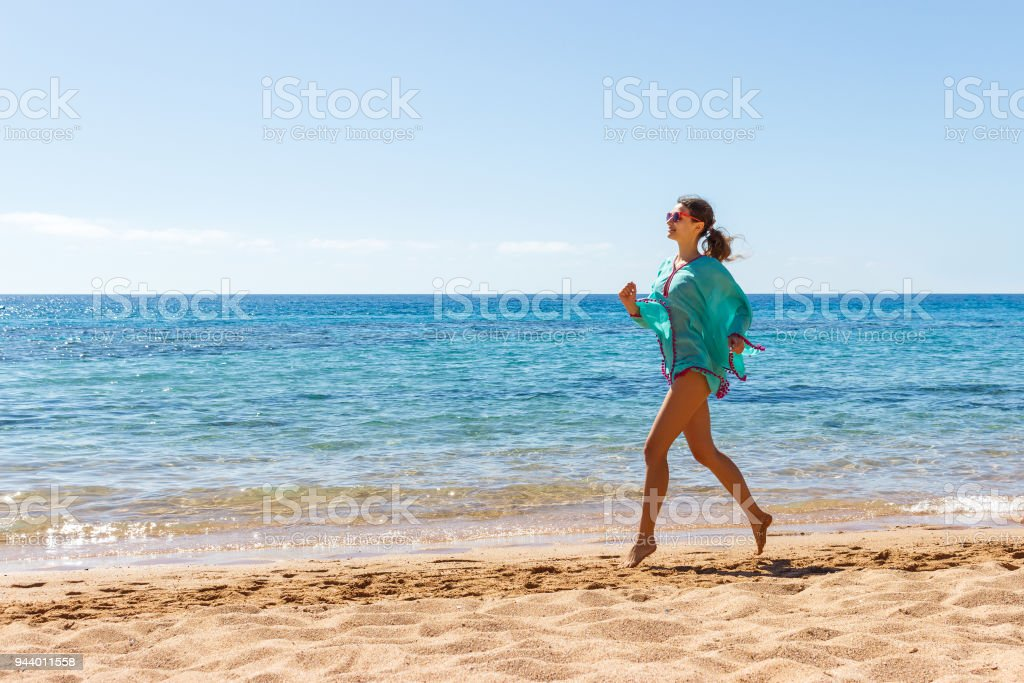 wooman runing on the beach in a sunny day. summer beach girl stock photo