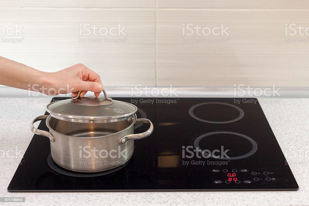 Woomen hand open a saucepan in modern kitchen stock photo