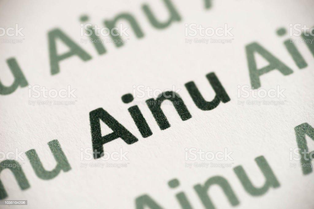 word Ainu language printed on paper macro stock photo