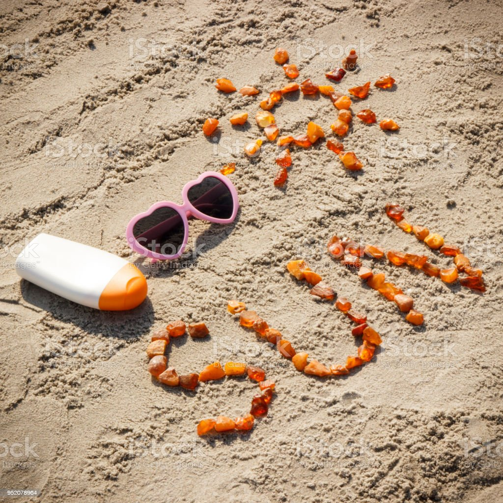 word and shape of sun sunglasses with sun lotion on sand at beach concept