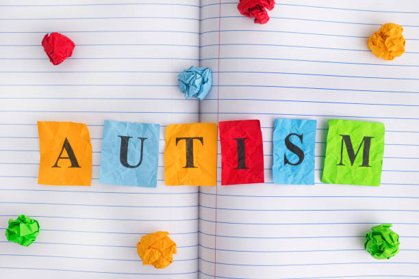 Word Autism on notebook sheet with some colorful crumpled paper balls around it stock photo