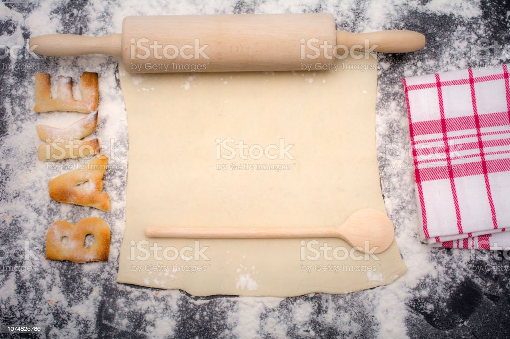 Word bake on working surface with rolling pin and lots of flour