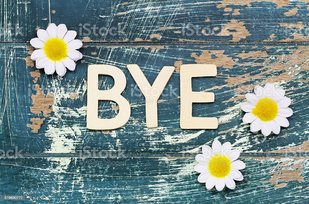 Word bye written with wooden letters on wood, white daisies stock photo
