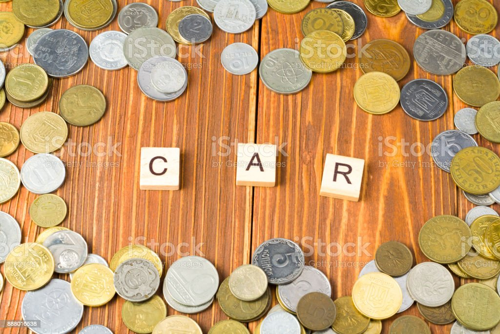 Word CAR on wooden cube with coins frame at wood background. Finance concept. stock photo