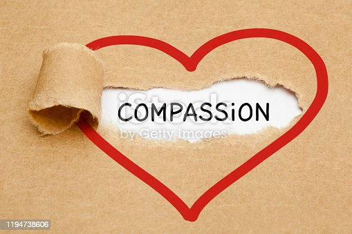Handwritten word Compassion appearing behind ripped red heart on brown paper.
