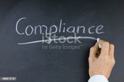 istock Word Compliance on Blackboard with Hand and Chalk 486915767