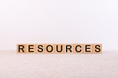 RESOURCES word concept written on wooden cubes lying on a light table and light background.