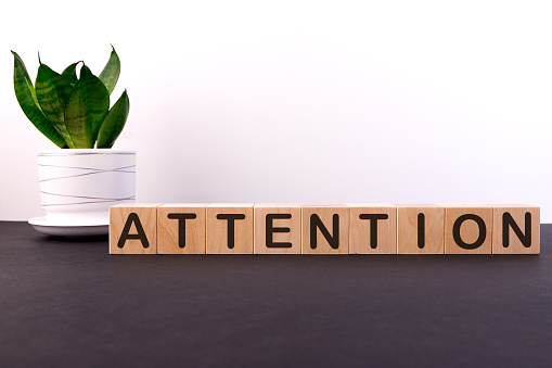 istock ATTENTION word concept written on wooden cubes on a dark table with a flower and a light background 1205911439