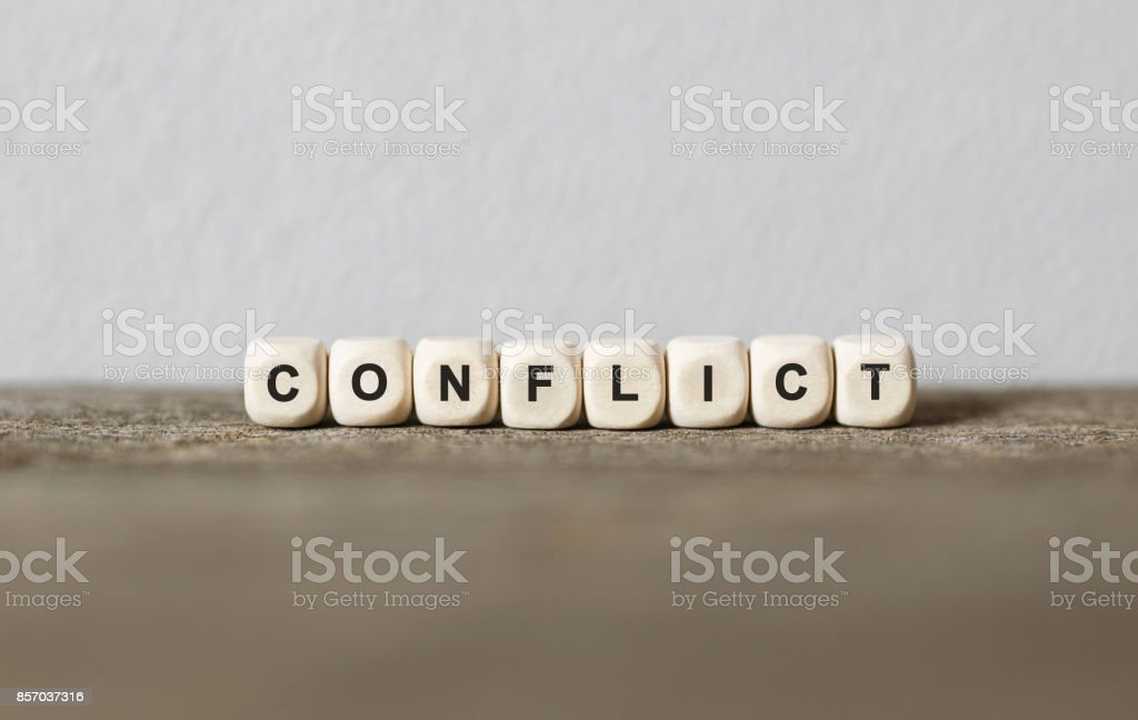 Word CONFLICT made with wood building blocks stock photo