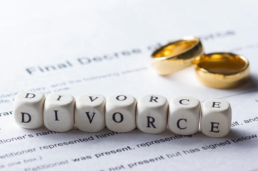 istock Word - Divorce made up of wooden letters on the table with wedding rings. 918843602