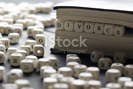 istock Word - Divorce made up of wooden letters on the table with wedding rings. 925552790