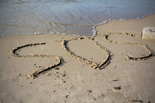 sos - word drawn on the sand beach with the soft wave - stranded stock pictures, royalty-free photos & images